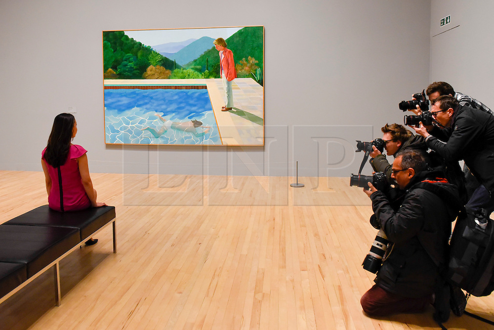 "© Licensed to London News Pictures. 06/02/2017. London, UK. Members of the media photograph a staff member viewing ""Portrait of an Artist (Pool with Two Figures)"" at the preview of the world's most extensive retrospective of the work of David Hockney at the Tate Britain, which will be on display 9 February to 29 May 2017. Photo credit : Stephen Chung/LNP"