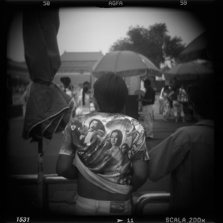 Asia, China, Beijing, Blurred black and white image of tourist wearing Jackie Chan T-shirt in the Forbidden City
