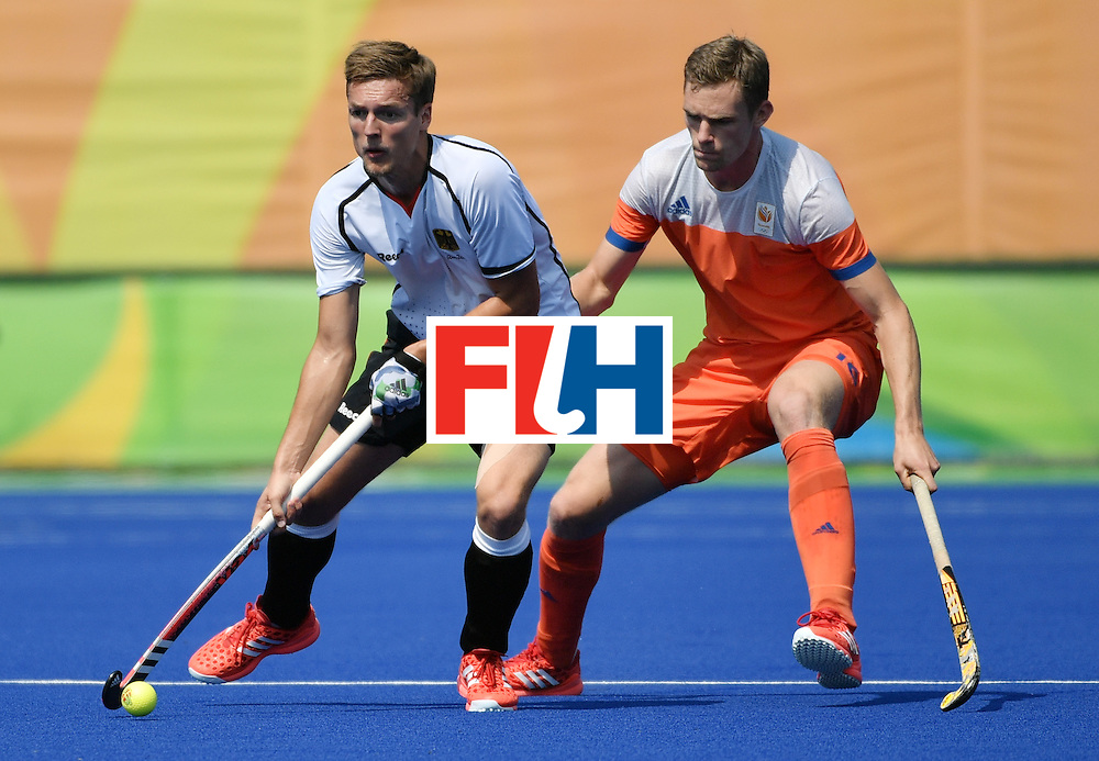 Germany's Mathias Muller (L) vies with Netherlands' Mirco Pruijser during the men's Bronze medal field hockey Netherlands vs Germany match of the Rio 2016 Olympics Games at the Olympic Hockey Centre in Rio de Janeiro on August 18, 2016. / AFP / Pascal GUYOT        (Photo credit should read PASCAL GUYOT/AFP/Getty Images)
