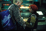 A male punk with bleached mohican and leather jacket and a female punk with dyed red hair and studded leather jacket inside fast food restaurant, U.K, 1990s.