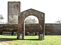 Italian medieval architecture in a church courtyard with arch and tower on backgerund beyond wall with stone coffins at the bottom