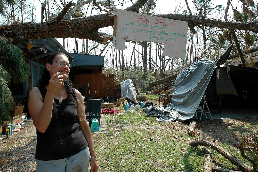"Pamela DeBaun smokes  acigarette under her for sale sign at her home in Bay St. Louis after Hurricane Katrina severely damaged and flooded her home. The sign reads""cut little fixer upper-handymans special-call 1-800-CALLFEMA"" Sept. 16,2005.Photo ©Suzi Altman"
