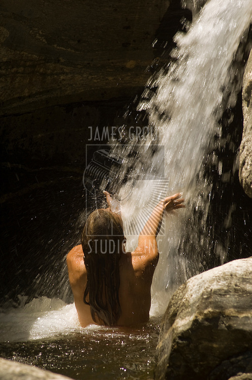Woman embracing water as it cascades from a waterfall