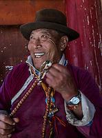 Senior tibetean community leader in the town stupa reciting prayers.