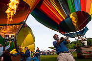 Jeff Ratcliffe, center, of Thompson, Conn., tethers a hot air balloon as it launches during the 35th Annual Quechee Hot Air Balloon Craft & Music Festival in Quechee, Vt., on June 15, 2014. After a weekend of waiting for the weather to clear, the festival finally saw a balloon launch on the last evening of the festival. (Valley News - Will Parson)