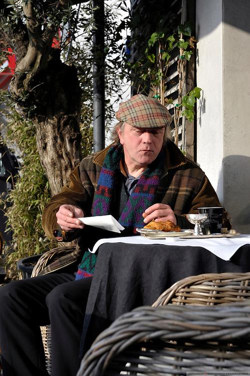 Gent, Belgie, Mar 14, 2009, Hedendaags kunstenaar Mugo neemt zijn ontbijt Bij Sint Jacobs, ©Christophe VANDER EECKEN