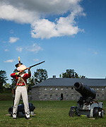 Tour guide dressed as soldier fires rifle leaving smoke in his face; Fort Lennox; Quebec Province, Canada