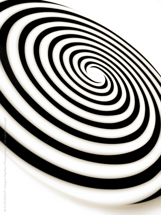 studio photograph of spinning disc with concentric circles, close-up, diagonal perspective predominantly black