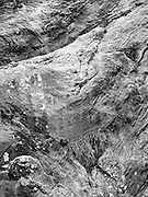 Black & white (B&W) rendition of a color photograph of granite folds in Milford Sound (Piopiotahi), Fiordland National Park, New Zealand