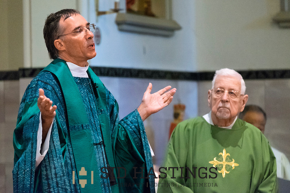 11 Oct. 2015 -- ST. LOUIS -- Father Vincent Nyman (left) and Permanent Deacon Rev. Mr. Donald L. Driscoll lead the service during Mass Mob IV at Our Lady of the Holy Cross in the Baden neighborhood of St. Louis Sunday, Oct. 11, 2015. Worshipers from across the Archdiocese of St. Louis gathered at the parish, founded in 1863 and meeting in a Gothic-style building dedicated in 1909. Photo © copyright 2015 Sid Hastings.