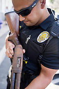 June 28, 2008 - PHOENIX, AZ: Phoenix police officer J. RAMIREZ clears a shotgun turned in during the gun bay back Saturday. The city of Phoenix conducted its first gun buy back program Saturday. People who turned in a functioning gun of any sort were given a card good for $100 worth of groceries at Basha's or Food City grocery stores in the Phoenix area. The program was funded by a donation of $10,000 worth of cards. All of the cards were given away within hours of the start of the program. Critics said the buy back was a sham, that only old, barely serviceable firearms would be turned in. Most of the guns turned in did appear to be old, but all were functioning. Photo by Jack Kurtz / ZUMA Press