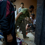 August 10, 2012 - Aleppo, Syria: Nurses give assistance to people, injured minutes earlier by heavy shelling from the Syrian Army against a bakery in the residential area of Tariq Al-Bab in central Aleppo. At least 12 people have died and more the 20 got injured during the attack.<br /> <br /> The Syrian Army have in the past week increased their attacks on residential neighborhoods where Free Syria Army rebel fights have their positions in Syria's commercial capital, Aleppo.