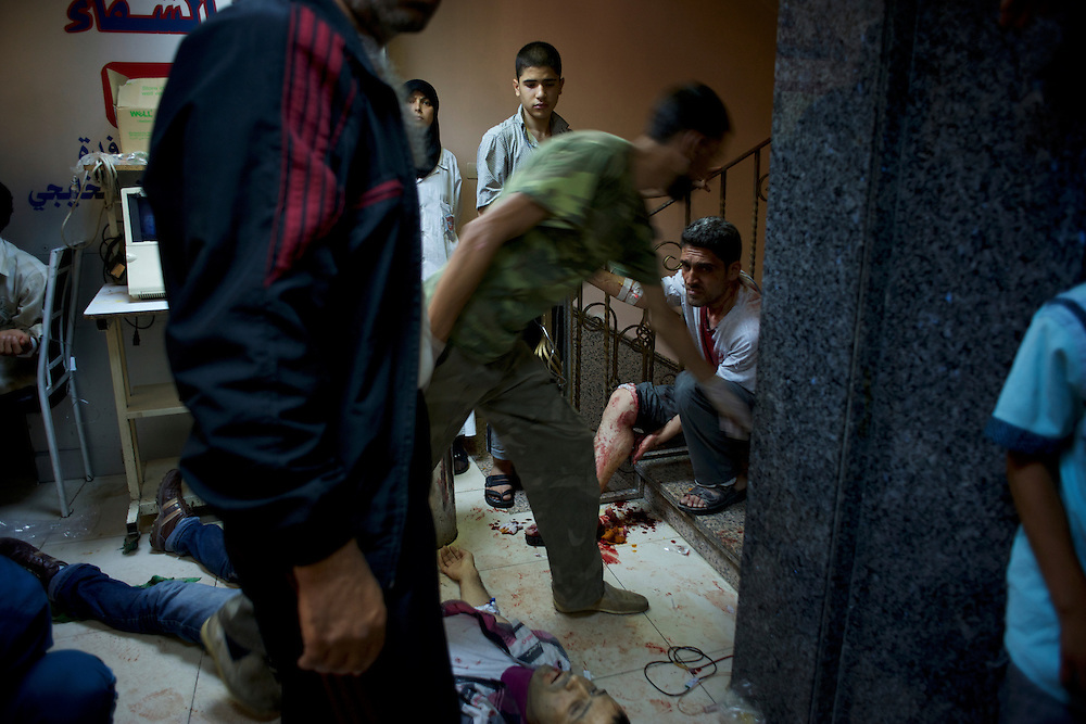 August 10, 2012 - Aleppo, Syria: Nurses give assistance to people, injured minutes earlier by heavy shelling from the Syrian Army against a bakery in the residential area of Tariq Al-Bab in central Aleppo. At least 12 people have died and more the 20 got injured during the attack.<br />