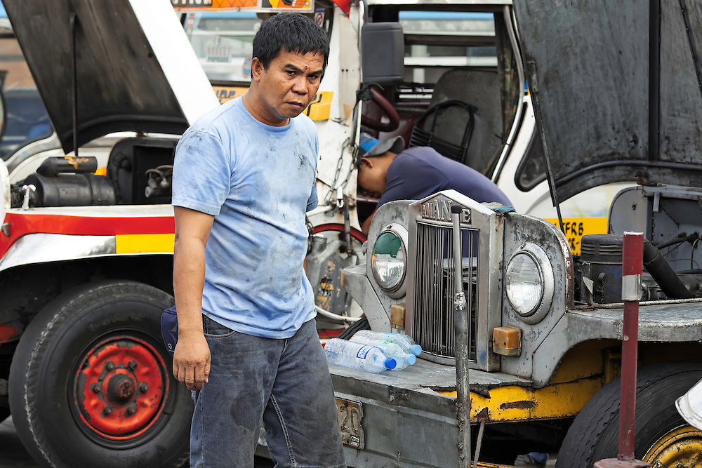 Mechanics work on Jeepney in Manila, Philippines. Copyright 2015 Reid McNally.