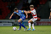 Alfie May of Doncaster Rovers challenges Matthew Virtue-Thick of Blackpool F.C. during the EFL Sky Bet League 1 match between Doncaster Rovers and Blackpool at the Keepmoat Stadium, Doncaster, England on 17 September 2019.
