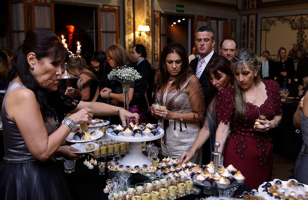 Carpeta 18 Foto 09<br /> Invitadas se sirven dulces durante la fiesta de un casamiento, Paraguay el 15 de abril de 2012. (Jorge Saenz)<br /> <br /> &quot;Todo era una Fiesta&quot;:<br /> Por mas crisis que ataquen la econom&iacute;a publica y privada, la clase alta de Paraguay tal como la de otros pa&iacute;ses, no limita en lo mas m&iacute;nimo su costumbre de festejar las bodas con una gran inversi&oacute;n econ&oacute;mica en los eventos. Este trabajo presentado es parte de uno mas general en desarrollo sobre la sociedad paraguaya llamado &quot;Las Clases&quot; desde hace mas de 10 a&ntilde;os.