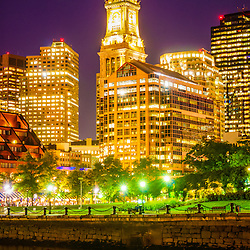 Boston cityscape at night along the Boston Harbor waterfront with Custom House Tower clock and downtown Boston buildings.