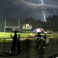(SPORTS) Jazlet 7/18/2003  Only but a few people stand on the Raritan H.S. field as a wicked bolt of lightning and then rain suspended play of the Allshore Football Classic game before the start of the third quarter.  The scoreboard shows the time score and period of play.    Michael J. Treola Staff Photographer..