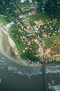"An aerial view of the pier and beachfront of Puerto Cabezas, in Bilwi, Nicaragua, a vacation destination for many Nicaraguans looking to enjoy the Carribean Coast. In 1961, the ""Bay of Pigs"" invasion of Cuba was launched from here. Its population soared during the Contra War due to fighting and Sandinista relocation programs. The port was critical during Sandinista rule for receiving Cuban and Soviet military aid. It is now the capital of RAAN."