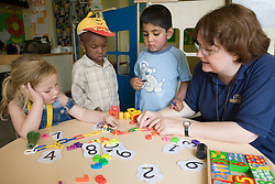 Nursery nurse helping children with numeracy skills,