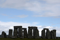 Visitors are dwarfed by the Stonehenge monument in England.  Stonehenge served as a burial ground from its earliest beginnings and for several hundred years thereafter.