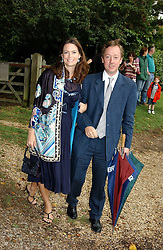 GEORDIE GREIG and his wife KATHERINE at the wedding of Tom Parker Bowles to Sara Buys at St.Nicholas Church, Rotherfield Greys, Oxfordshire on 10th September 2005.<br />