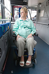 Woman sitting on bus in designated area for wheelchair users looking out the window,