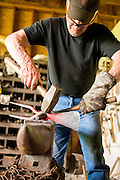 Bob Denman hammers a piece of hot metal to make a Magna Grecia garden tool.