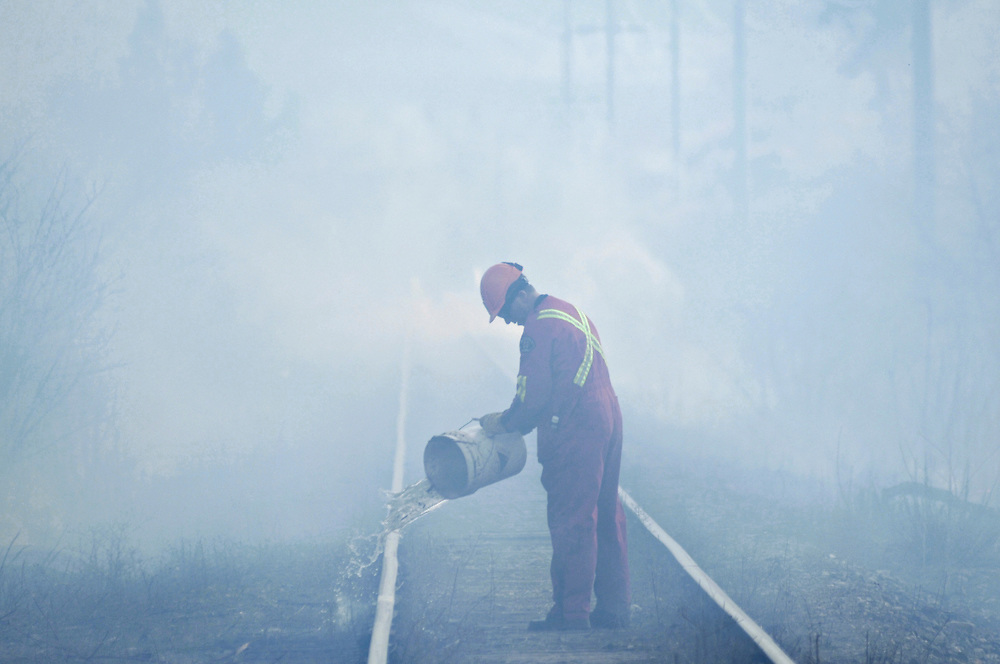 A Kelowna firefighter uses a bucket to douse hotspots along a railway in Kelowna after a rank 3 fire threatened nearby businesses.