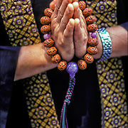 Close up of hands of Buddhist Monk mediationg holding prayer beads