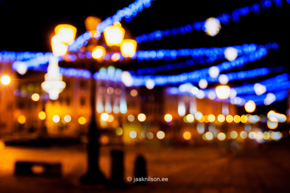 Laterns and blurred city lights.  Tartu town hall square in Estonia. Lighted, illuminated bokeh.