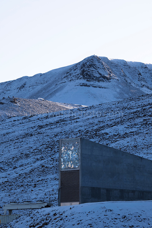"""Nestled into the rocky waste of plataberget Mountain about Svalbard's airport, the Global Seed Vault is at once startling and innocuous. Designed by architect Peter W. Søderman at Barlindhaug Consulting, this concrete, steel and glass structure is the first layer of security to a repository of millions of seeds from around the world, stored here in case of disaster, disease, or war...The Svalbard Global Seed Bank is situated 120 metres (390 ft) inside a sandstone.mountain at Longyearbyen on Spitsbergen Island, in the Svalbard archipelago about 1300km from the North Pole. Svalbard was considered ideal for the bank, due to low tectonic activity and its permafrost, which will aid preservation. Even if sea levels rise due to climate change - and the melting of ice caps, the seeds will be safe and dry , as they are stored at a location 130 metres (430 ft) above sea level. ..The Svalbard Global Seed Vault  provides a safety net against accidental loss of diversity from traditional storage within genebanks around the world, and has a capacity for 4.5 million seeds. Although the media has made much of the """"Doomsday Vault's"""" role in providing security in the face of war or or catastrophe, the operators - the Norwegian government  and the Global Crop Diversity Trust and the Nordic Genetic Resource Center - say that it will be most useful when genebanks lose samples due to mismanagement, accident, equipment failures, funding cuts and natural disasters."""