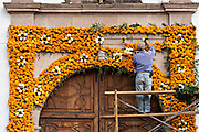 A Mexican man places marigolds on an ofrenda on the door to the Templo de Nuestra Señora del Sagrario church for the Day of the Dead festival in Santa Clara del Cobre, Michoacan, Mexico.