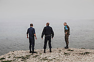 Greek police officers with a Polish counterpart (R) acting with European border agency Frontex watch the Aegean sea near Mytilene, Greece on 02 March, 2016. Lesbos, the Greek vacation island in the Aegean Sea between Turkey and Greece, faces massive refugee flows from the Middle East countries.
