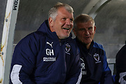 AFC Wimbledon temporary manager coach Glyn Hodges smiling whilst sat in the dug out during the Leasing.com EFL Trophy match between AFC Wimbledon and Leyton Orient at the Cherry Red Records Stadium, Kingston, England on 8 October 2019.