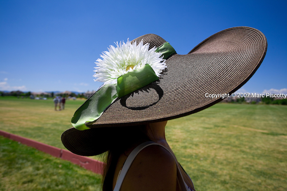 SHOT 7/22/2007 - Dana Ottenbreit of Denver was one of the many women who were both fashionable and cool in their hats during Smith Barney Championship Day Sunday July 22, 2007 at the 20th Annual Denver Polo Classic at the Polo Reserve Development near Mineral and Santa Fe in Littleton. Ottenbreit said it was her third or fourth year at the event and said the hat definitely helped keep her cooler in the scorching July heat of the day. The 2007 Denver Polo Classic Presented by Avanade is the largest charity polo event in the U.S. Throughout the three-day weekend, four teams comprised of local, regional and international polo players will compete to play on championship day for the coveted Denver Polo Cup trophy. To date the event has raised more than $2 million for Colorado?s disadvantaged children and the charities that serve them. Team BKD won the Denver Polo Cup trophy with a 13-11 overtime victory over Team Avanade..(Photo by Marc Piscotty / © 2007)