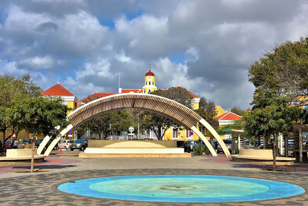Wilhelmina Park in Punda, Eastside of Willemstad, Curaçao  <br /> This terraced bandstand and fountain are part of the Wilhelmina Park in Punda.  Its namesake is Wilhelmina Helena Pauline Marie. She was the Queen of the Netherlands from 1890 until 1948. Her 58 year rule qualified her as the longest reigning Dutch monarch. She was also the last member of the House of Orange-Nassau when she died in 1962.  In the background is the Fort Amsterdam church clock tower.