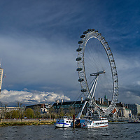 The London Eye is a giant Ferris wheel located on the South Bank of the River Thames in London, England.  It is also known as the Millennium Wheel.  Since mid-January 2015, it has been known as the Coca-Cola London Eye.