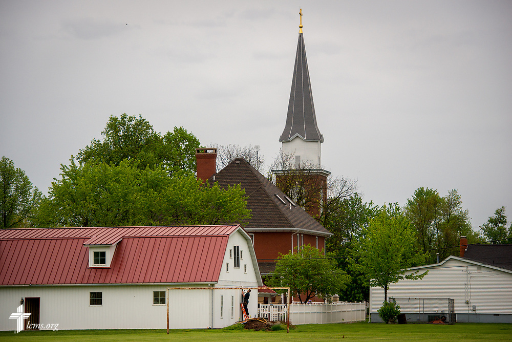 A man works on a barn set against Zion Lutheran Church and School, Staunton, Ill., on Wednesday, April 26, 2017. LCMS Communications/Erik M. Lunsford