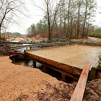 Thomas Wells   BUY AT PHOTOS.DJOURNAL.COM<br /> Resident atthe Nettleton Fox Hunting and Fishing Association uses a piece of wood to cross the bridge that was washed out on Friday following a nearby levee collapse at Lake Whiteside.