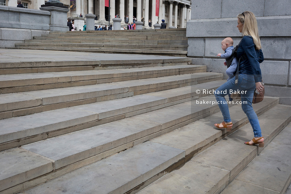 A mother carries her young child up the steps in front of the National Gallery in Trafalgar Square, on 15th June 2019, in London, England.