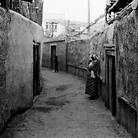 HOTAN, 2 OCOTBER 2001: a pregnant Uighur woman stands in a lane in Hotan's Uighur district.Uighurs live in less developped districts than Han Chinese...Uighur muslims in southern Xinjiang province lead very basic lifestyles and have an average monthly income of about 50 US$.. . .  . .