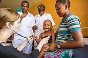 Dr Siobhan Neville examines 14 month old Jennifer on the children's ward during the daily rounds.  The rounds are attended by all the medical staff who work on that ward, doctors, nurses and attendants.  St Walburg's Hospital, Nyangao. Lindi Region, Tanzania.