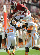 Decatur Daily/Gary Cosby Jr.   Alabama wide receiver Kevin Norwood leaps over Tennessee defensive back JaRon Toney and Tennessee defensive back LaDarrell McNeil as he runs after making a catch on a pass during the first half of the Alabama-Tennessee game Saturday in Tuscaloosa.
