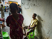 15 AUGUST 2016 - BANGKOK, THAILAND: Residents of the Pom Mahakan slum wait for city officials to deliver eviction notices to the community. Final eviction notices were posted today and residents of the slum have been told they must leave the fort by September 3, 2016. The Pom Mahakan community is known for fireworks, fighting cocks and bird cages. Mahakan Fort was built in 1783 during the reign of Siamese King Rama I. It was one of 14 fortresses designed to protect Bangkok from foreign invaders. Only two of the forts are still standing, the others have been torn down. A community developed in the fort when people started building houses and moving into it during the reign of King Rama V (1868-1910). The land was expropriated by Bangkok city government in 1992, but the people living in the fort refused to move. In 2004 courts ruled against the residents and said the city could take the land.      PHOTO BY JACK KURTZ