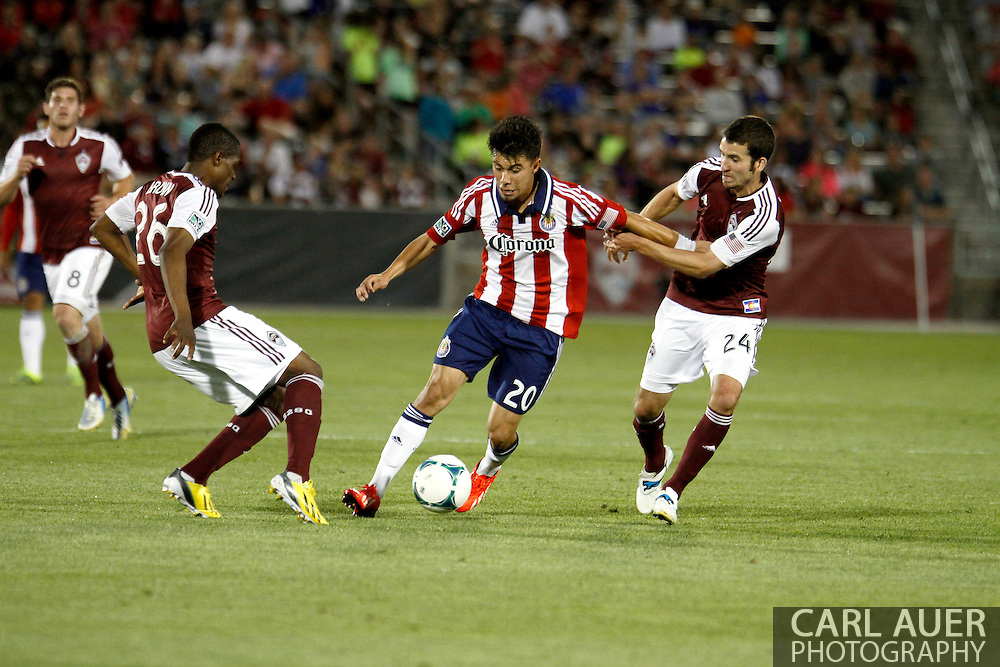 May 25th, 2013 Commerce City, CO - Chivas USA midfielder Carlos Alvarez (20) dribbles the ball against the defense by Colorado Rapids midfielder Nathan Sturgis (24) and forward Deshorn Brown (26) in the second half of the MLS match between Chivas USA and the Colorado Rapids at Dick's Sporting Goods Park in Commerce City, CO