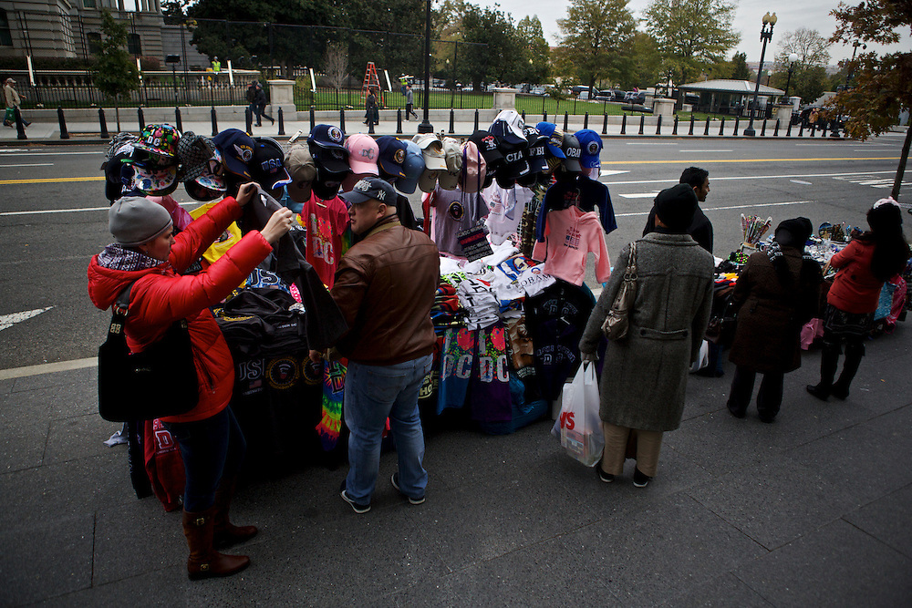 Tourists lookover memorabilia from a street vendor near the White House on Nov. 7, 2012 in Washington, D.C.
