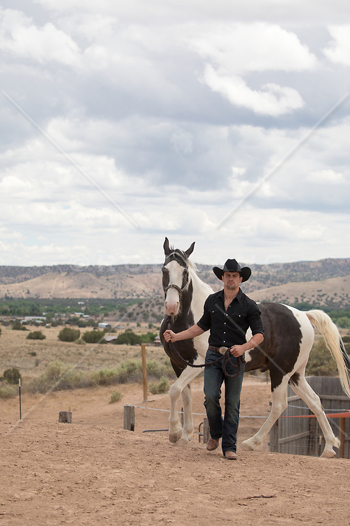 cowboy walking with his horse on a ranch
