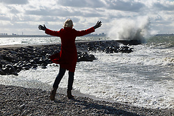 Woman standing on Merivälja pier in Tallinn. Storm waves. Outstretched arms.