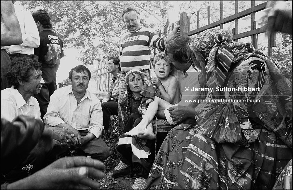 ROMANIAN ORTHODOX EASTER CELEBRATIONS, THE MOST IMPORTANT HOLIDAY OF THE YEAR FOR THE GYPSIES. PUIA MIHAI CRIES IN HIS FATHERS ARMS AFTER BEING TAKEN TO A HOSPITAL WHEN IT WAS DISCOVERED HE'D DRANK A LITRE OF WINE. SINTESTI, ROMANIA, EASTER 1994..©JEREMY SUTTON-HIBBERT 2000..TEL./FAX. +44-141-649-2912..TEL. +44-7831-138817.